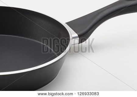 Side view of empty frying pan with coating on white background. The fastening of the handle.