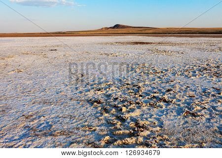 Salt crust on the surface of the desert and the lonely mountain.Evening landscape. The extraction of salt.