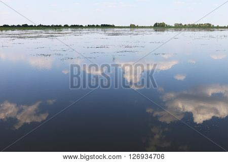 Blue summer sky and reflection of clouds in the surface of the Volga river. Nature landscape view in Russian countryside.