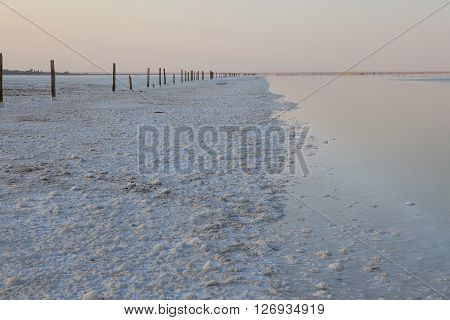 The surface of the lake with very salty water and wooden pillars and a salt crust on the surface of the desert and the lonely mountain.