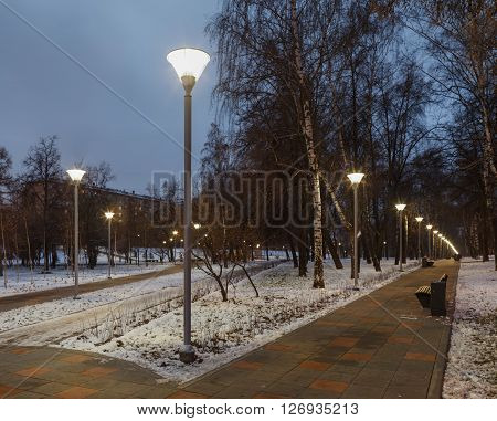 Evening lighting in winter urban. Long walkway with street lamps. City lights and illuminators. Russia Moscow.