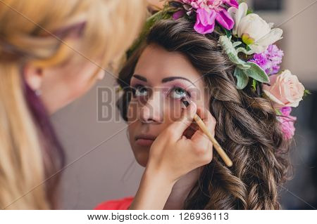 The visagist is applying wedding makeup. The bride closed her eyes.Wedding dress with hairstyle and bright makeup