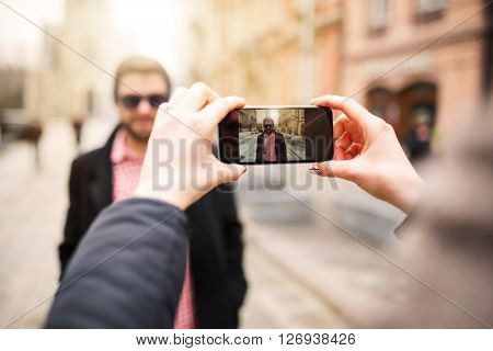 A photo of girl taking a photo of young man by her mobile phone.