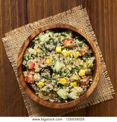 Quinoa salad with sweet corn olive tomato cucumber and chives in wooden bowl photographed overhead on dark wood with natural light (Selective Focus Focus on the top of the salad)