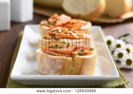 Smoked salmon sandwiches with chives photographed with natural light (Selective Focus Focus on the front of the salmon on the first bread)