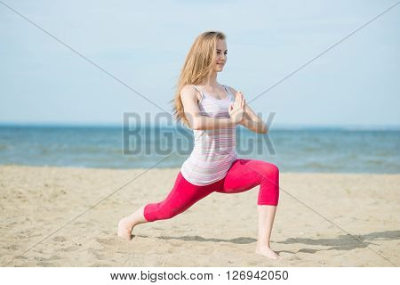 Young lady practicing yoga. Beautiful woman posing at the summer sand beach. Workout near ocean sea coast. Beautiful fit tan girl. Fitness model caucasian ethnicity outdoors. Weight loss exercise. Meditation.