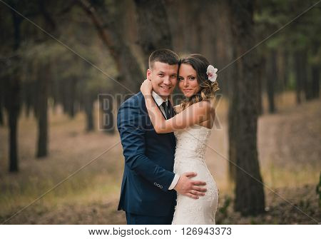Bride and groom at wedding day walking outdoors in summer time. Bridal couple, Happy Newlywed woman and man. Loving wedding couple outdoor. Bride and groom