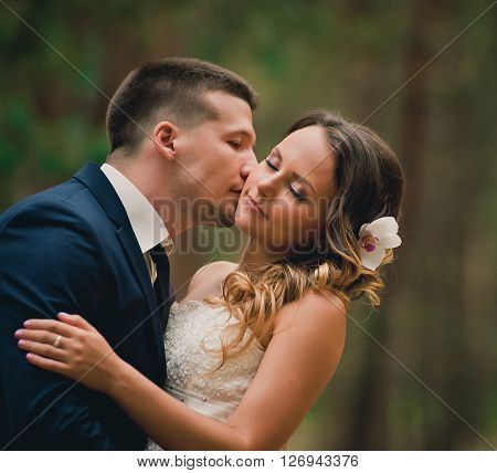 Bride and groom at wedding day walking outdoors in summer time. Bridal couple. Happy newlywed woman and man. Loving wedding couple outdoor. Bride and groom