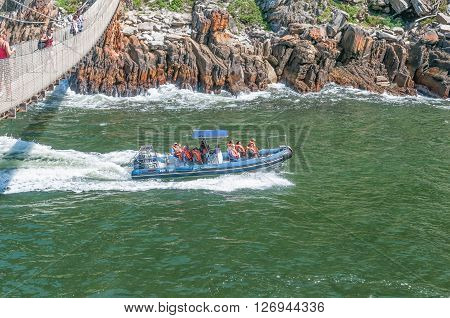 STORMS RIVER MOUTH SOUTH AFRICA - FEBRUARY 29 2016: Unidentified tourists on an inflatable speedboat passing underneath the suspension bridge to enter the Storms River gorge