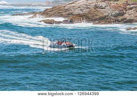 STORMS RIVER MOUTH SOUTH AFRICA - FEBRUARY 29 2016: Unidentified tourists on an inflatable speedboat entering the mouth of the Storms River