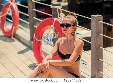 Sexy young curly woman relaxing near life-saving buoy. sexy girl in bikini seat near swimming pool. Woman sunbathing in bikini at tropical resort. Outdoor summer portrait of sexy girl ** Note: Visible grain at 100%, best at smaller sizes