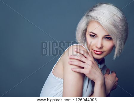 beautiful young blond woman with brown eyes against grey studio background