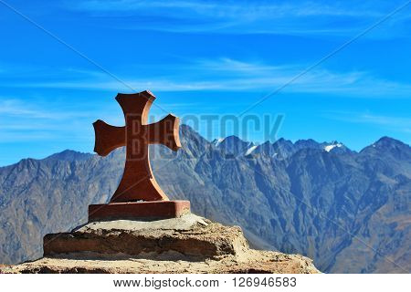A cross on the summit of a mountain.