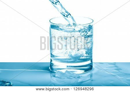 Sparkling water pouring into glass over bright background. Cold drink. Blue colored picture