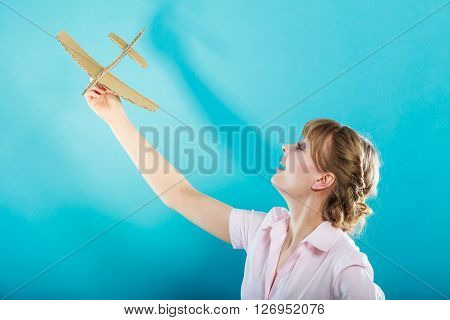 Summer holidays and tourism concept. attractive business woman enjoying life daydreaming thinking about vacation holding paper toy airplane in hand on blue