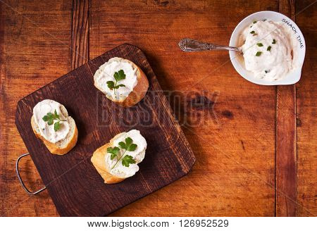 Snack time with tasty baguette sandwiches and savory cream on a wooden table