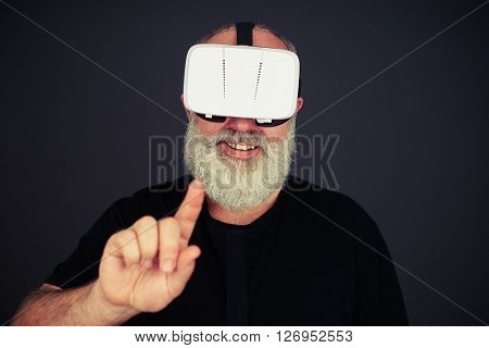 Smiling senior man touch something with his left hand using virtual reality glasses