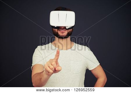 Beard man touch something with his right hand using virtual reality glasses, on black background