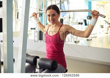 Beautiful Caucasian smiling woman is working out on pull-down machine in gym near mirror