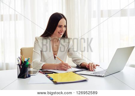 Smiling woman working on her laptop and writing some data in her pad in white office