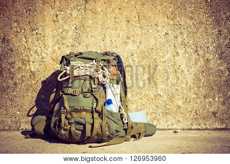 Hiking backpack camping and mountain exploring tourist equipment outdoor on grunge wall. Adventure summer tourism active lifestyle