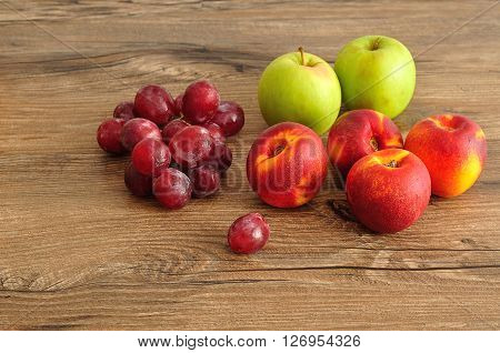 Apples, nectarines and grapes displayed on a wooden background