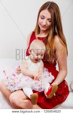 Single parent concept. Young elegant mother with baby girl in dress on mommy knees. Parenthood.
