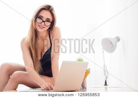 Positivity in mind. Delighted seductive smiling woman sitting on the table and using laptop while looking at you