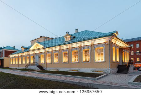 A single storey building in classical palladio style with yellow walls and evening architectural lighting. Moscow Russia