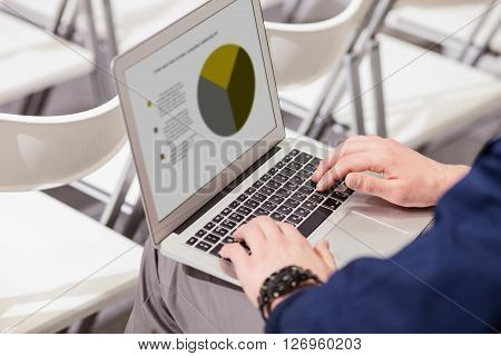 Close up of male hands typing on a laptop in auditory hall. The man is sitting and holding a computer on his knees