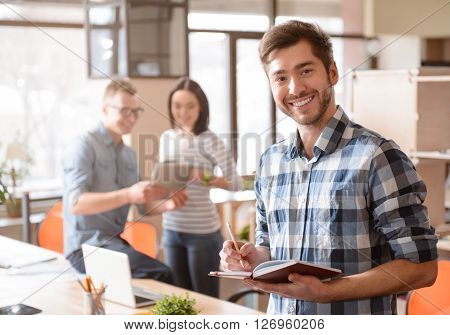 Elated mood. Cheerful smiling handsome man holding notebook and standing in the office while his colleagues talking in the background