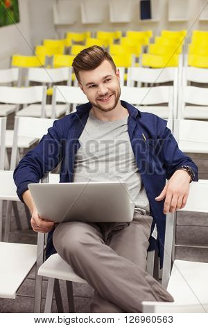Attractive man is sitting in auditory hall and holding a laptop. He is looking forward and flirting with someone. The student is smiling