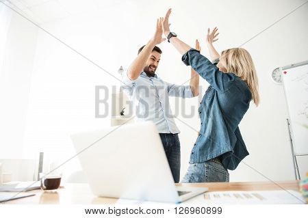 We have done it. Cheerful young man and woman are happy for results of their work. They are giving high five and smiling. Colleagues are standing in office near a laptop