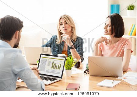 Cheerful young three colleagues are working in cooperation. They are sitting at the desk and smiling