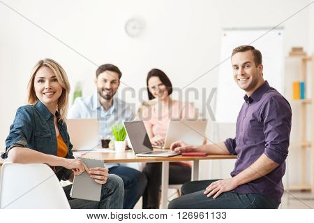 Pretty creative team is working together in office. They are sitting at table and smiling. The men and women are looking forward happily