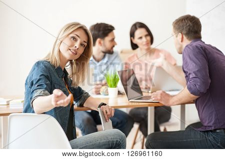 Join us and share your ideas. Pretty young woman is sitting and stretching her arm with invitation. She is looking at camera and smiling. Her colleagues are sitting and talking