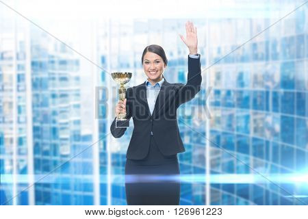 Portrait of businesswoman with cup, blue background. Concept of win and success