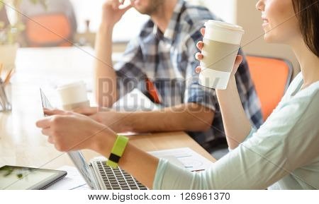 Have a rest. Cheerful pleasant positive colleagues drinking coffee and sitting at the table while being in the office