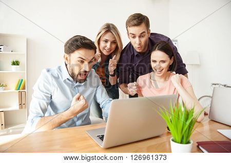 Cheerful creative team is waiting for results of their work with hope. They are looking at the laptop with anticipation and smiling. The men and women are holding fists
