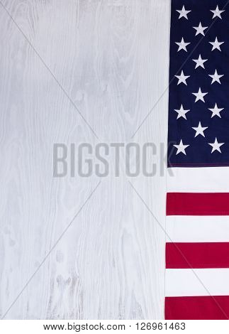 Folded cloth flag right border of United States of America on white wood in vertical format.