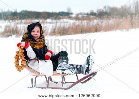 little girl in a fur coat with bagels on sledge