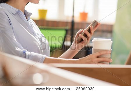 Get some relaxation. Pleasant nice girl sitting at the table and using cell phone while drinking coffee