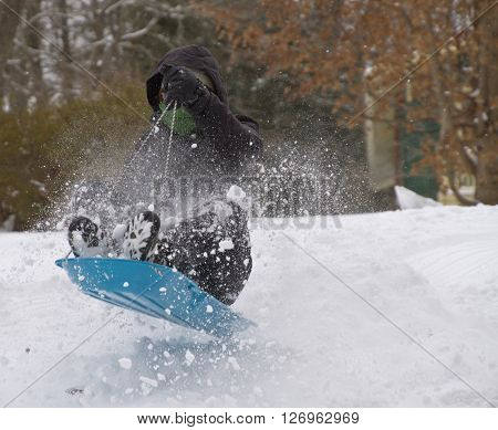 A bundled up youth sleds down a hill and over a bump in a wild and airborne spray of snow in winter