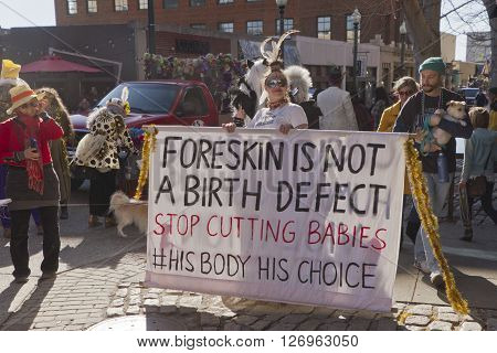 Asheville, North Carolina, USA - February 7, 2016: Costumed young woman holds large sign about circumcision saying