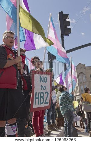 Asheville, North Carolina, USA - April 2, 2016: Crowd holds signs and waves symbolic flags to protest the new North Carolina HB2 Law that restricts the rights of those who are gay or transgender