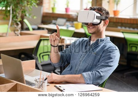 I see new world. Cheerful handsome pleasant  man sitting at the table and expressing positivity while wearing virtual reality device