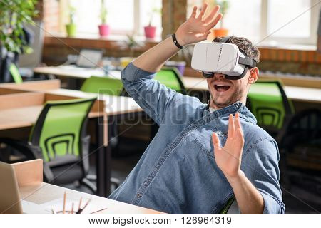 Unforgettable emotions. Cheerful emotional handsome  man sitting at the table and using virtual reality device while using gesture
