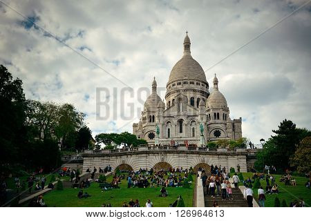 PARIS, FRANCE - MAY 13: Sacre Coeur Cathedral and tourists on May 13, 2015 in Paris. With the population of 2M, Paris is the capital and most-populous city of France