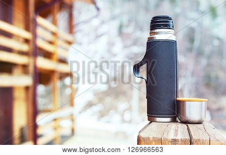 Steel thermos in black leather cover with a cup, outdoors