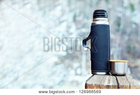Steel thermos in black leather cover with cup outdoors against the backdrop of the snow slope